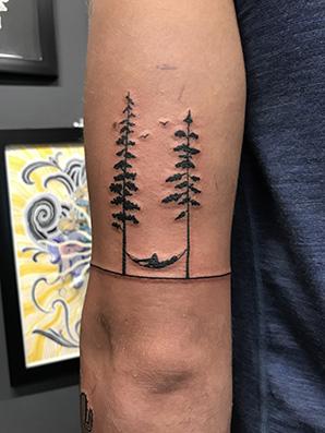 blackwork trees tattoo on tricep